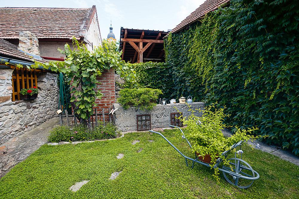Hrnčeky ačajníky zdobia ploty imúriky. Čaro záhrady tkvie hlavne vo vidieckych dekoráciách. Chvíľami máte pocit, akoby tu zastal čas. Vmodranskej záhrade ľahko splyniete sprírodou.