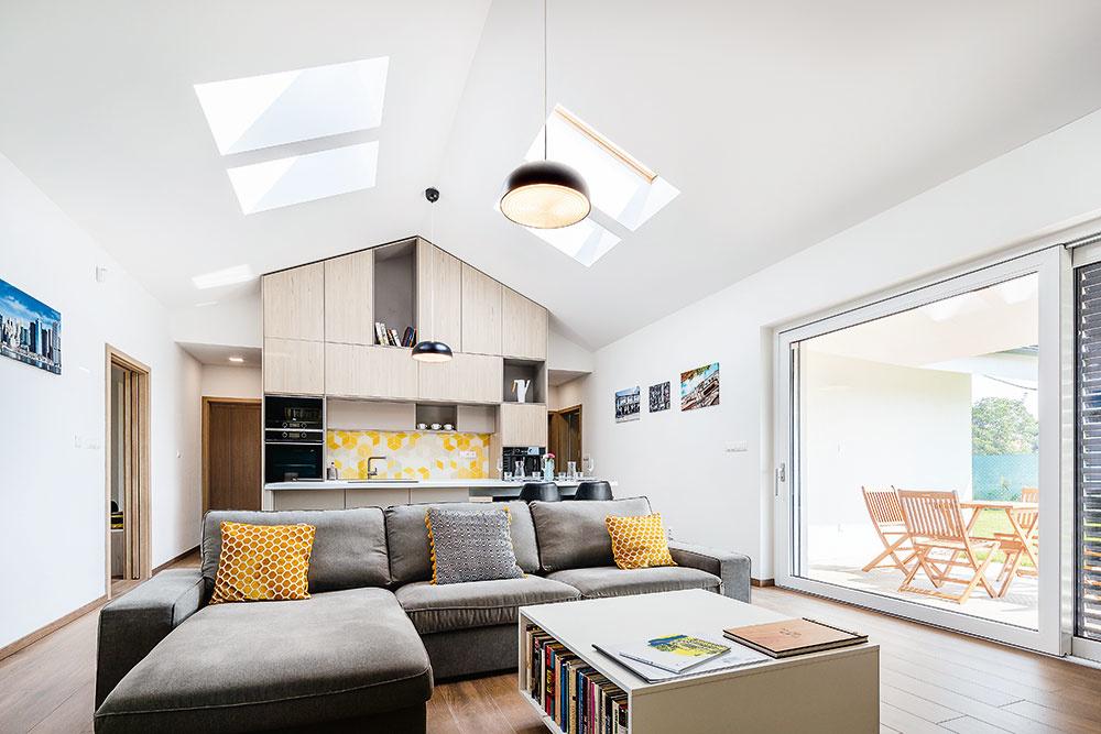 Centrom domu – dispozičným aj funkčným – je otvorený denný priestor, vktorom sa spájajú úlohy obývačky, kuchyne ajedálne. Cez zasklený portál je táto miestnosť prepojená aj so záhradou.