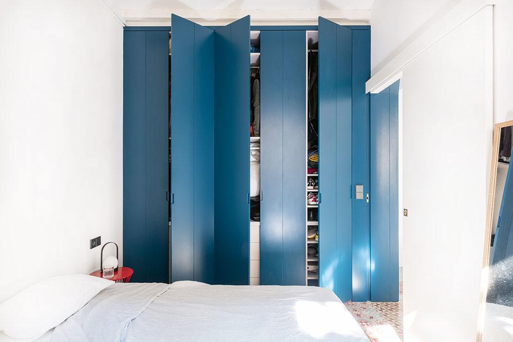 NA STENE VEDĽA POSTELE sú na mieru robené skrine, ktoré slúžia ako celoročný šatník. Na celkom obyčajných bielych dverách sú prilepené drevené drážkované panely natreté namodro. Rozhodne krajšie riešenie ako tzv. rolldor, čo poviete?