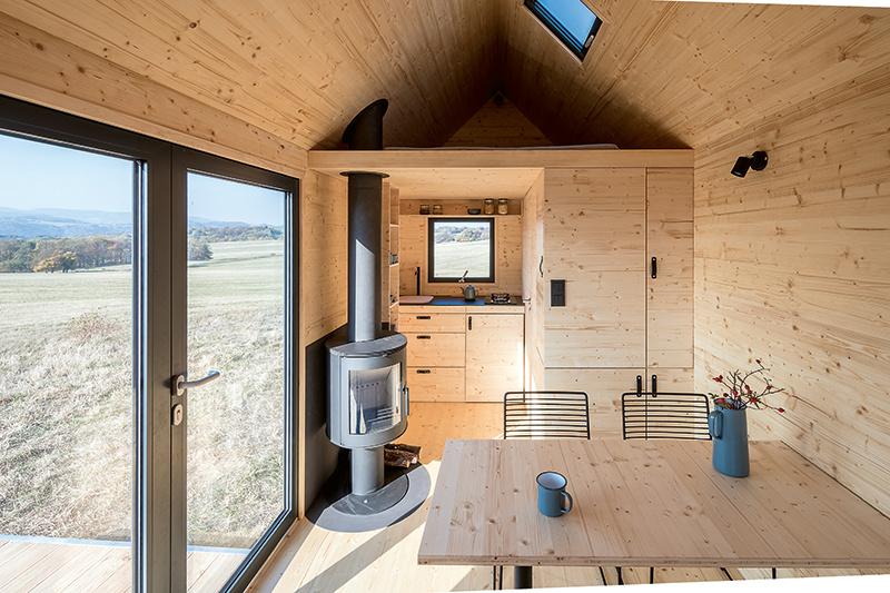 Interiér je vyriešený veľmi prakticky a vďaka variabilnému nábytku sa dokáže prispôsobiť rôznym funkciám, takže na 15 m2 máte v podstate byt veľkosti 2 + kk. Štýlovým srdcom príjemného drevom obloženého priestoru sú kozubové kachle na drevo.