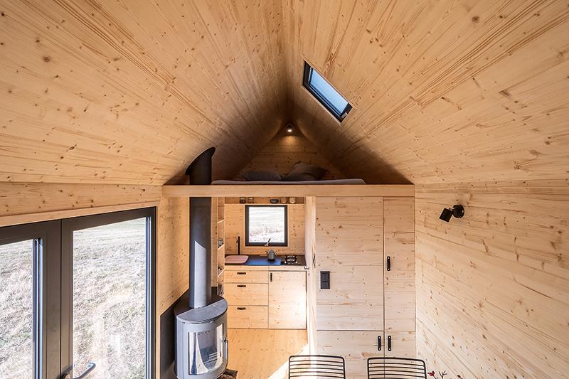 Mobilný dom so sedlovou strechou, hliníkovou fasádou a interiérom z dreva
