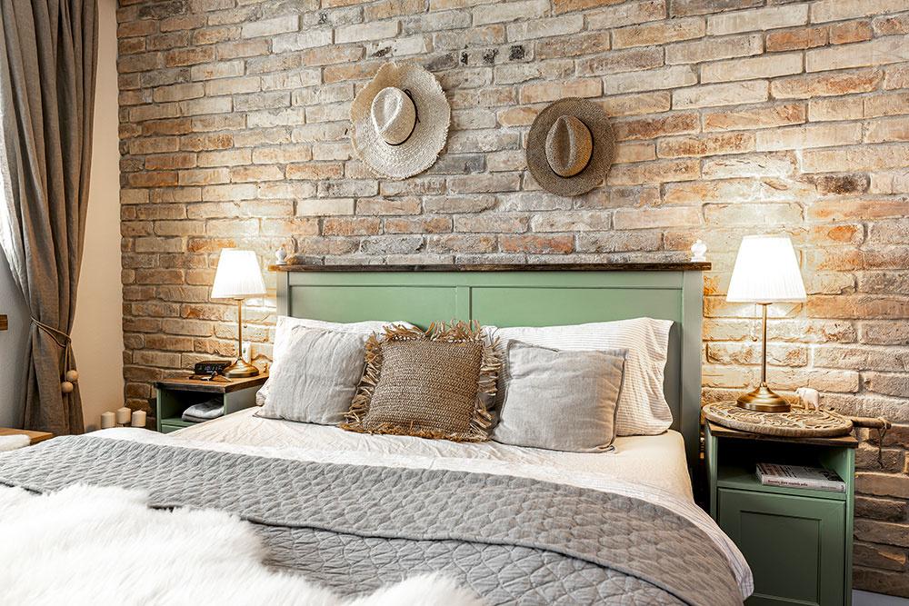 """Na stene za posteľou pribudol túto zimu obklad zpásikov narezaných zo starých tehál. """"Obkladali sme to asi týždeň atuším sme sa za ten čas aj dvakrát rozvádzali,"""" smeje sa Danka. """"Ale keď bolo všetko hotové, bol nakoniec manžel rád."""""""