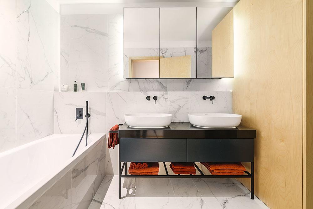 """Kúpeľni dodáva eleganciu mramorový obklad vkombinácii stmavomodrou ačiernymi detailmi, vrátane batérií. """"Udržiavajú sa lepšie než chrómové – kvapky avodný kameň na nich vidno omnoho menej,"""" upozorňuje Ingrid."""