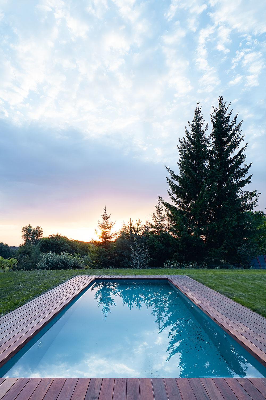 Do záhrady zvolili dreviny, ktoré sa bežne vyskytujú vokolí, tak, aby pozemok nenásilne splynul sokolitou prírodou. Jej súčasťou je aj 10 m dlhý vonkajší bazén. Vodu vňom ohrieva tepelné čerpadlo, ktoré slúži aj na vykurovanie domu.