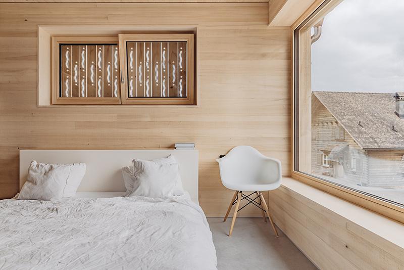 Spálňa v drevostavbe s veľkým oknom