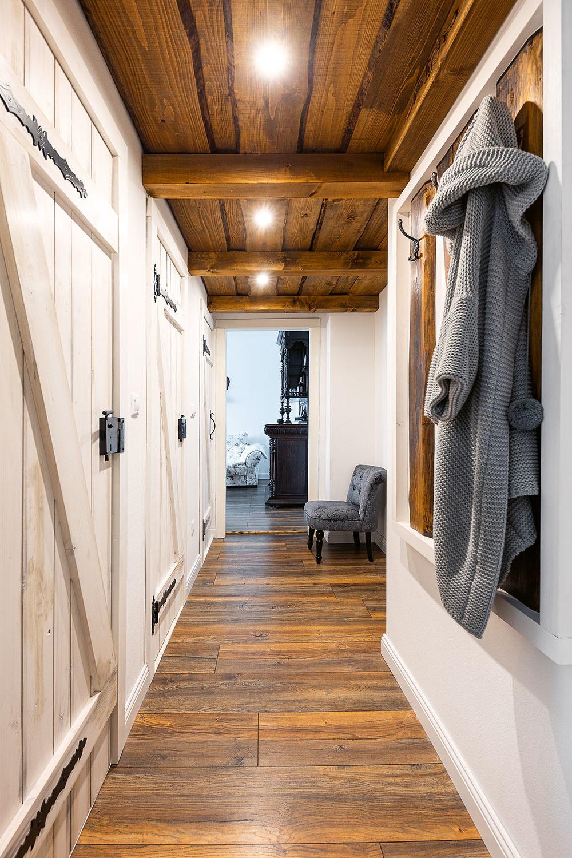 """Štýlový drevený strop vniesol do predsiene rustikálnu útulnosť azároveň je nad ním ukrytý odkladací priestor s""""padacími dverami"""". """"Úložného priestoru treba veľa achceli sme to vymyslieť tak, aby sme si byt nezapratali skriňami. Takéto miesto na veci, ktoré nepotrebujete denne, sa vždy zíde,"""" konštatuje Michal."""