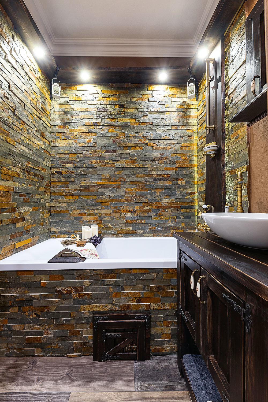 Tmavým kamenným obkladom chceli manželia navodiť vkúpeľni pocit ako vo wellness. Tmavý odtieň stien apodlahy odľahčuje biela sanita.