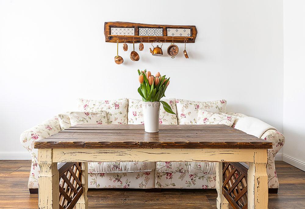 Zariadenie obývačky sa nesie vrovnakom duchu ako nábytok vkuchynskej časti otvoreného denného priestoru – vrovnakom štýle aj farebnosti urobili domáci príručný stolík, na polici na medený riad použili obkladačky, ktoré im ostali zkuchyne. Sedačka snežným kvetovaným poťahom je ako vystrihnutá zanglického vidieckeho interiéru.