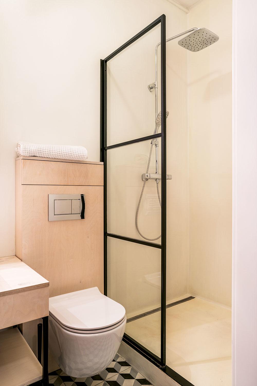"""Nekonvenčné riešenia nájdete aj vkúpeľni – napríklad namiesto klasických obkladačiek či sprchovej vaničky tu použili epoxidový náter. """"Keď sa poškodí, pretrie sa nanovo. Je to také trochu 'punkáčske' riešenie,"""" smeje sa Marek. Vpláne bol síce sprchový kút vrovine spodlahou, no vstarom dome sa tento zámer nedal zrealizovať."""