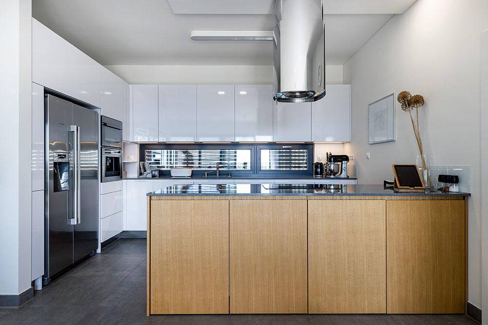 Moderná kuchyňa vbielom lesku aantikore bola majiteľkiným snom. Zo strany obývačky ju zjemňuje obklad zteplého dubového dreva avytvára tak kontrast kchladným spotrebičom apracovnej doske zkompozitu.