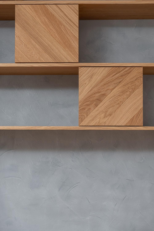 Úložný priestor rieši pod stropom zavesená sústava políc so skrinkami v šachovnicovom vzore.