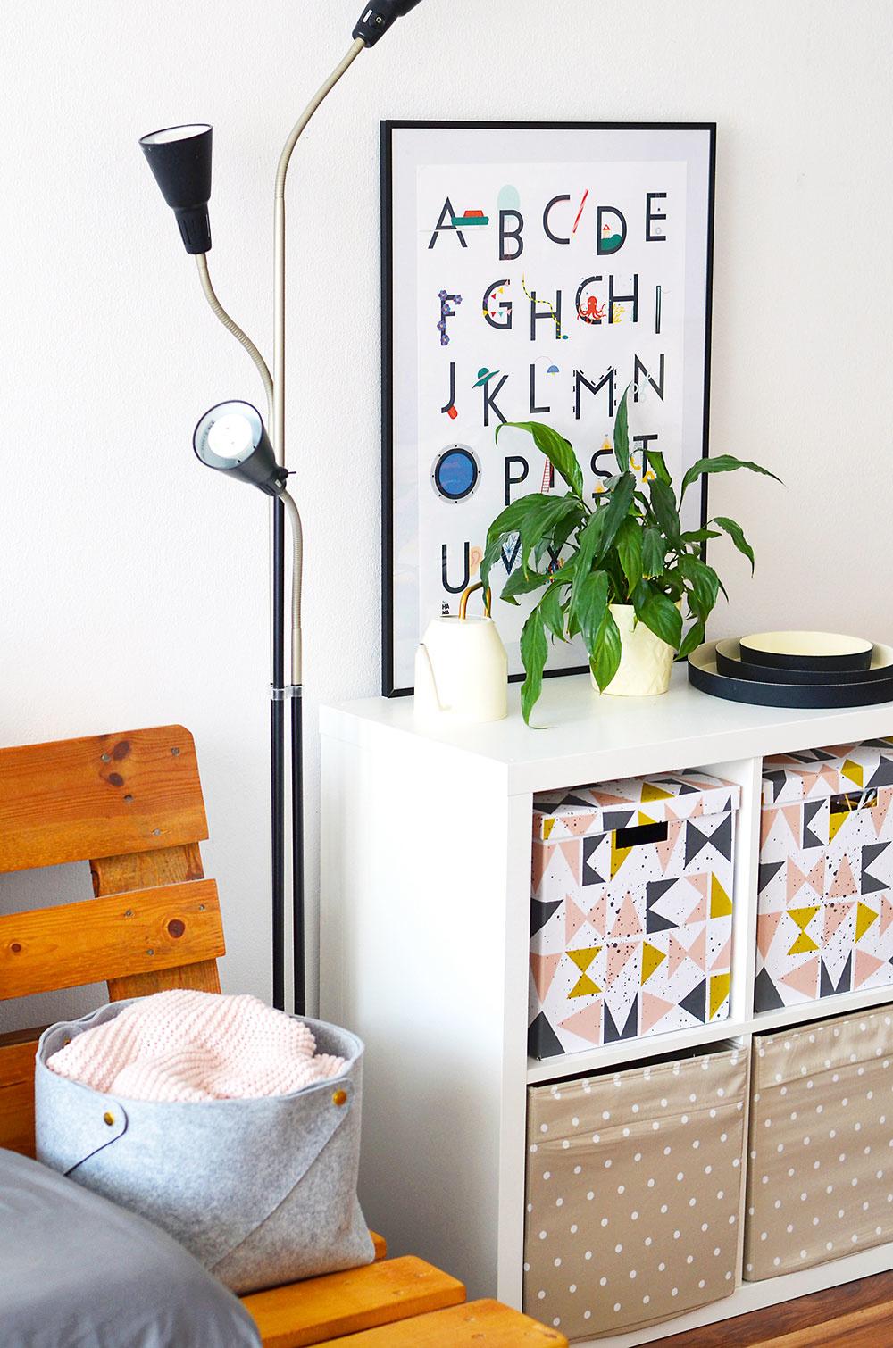 Bez zásuviek advierok. Jednoduchá zostava KALLAX doplnená oškatule aboxy pojme všetko dôležité, čo manželia vobývačke potrebujú. Zároveň vytvára príjemné zátišie, po akom Nina túžila. Väčšina dekorácií je zIkey, abecedový plagát je od slovenskej autorky byHANA.