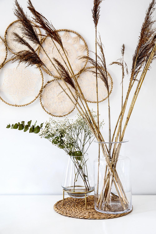 Číre sklenené vázy na ratanovej kuchynskej podložke s niekoľkými suchými rastlinami, v pozadí na stene vlastnoručne vyrobená nástenná dekorácia