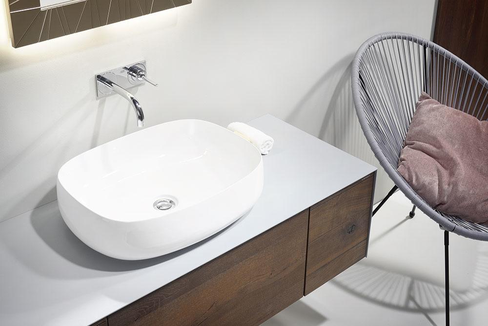 Krycia doska na umývadle je veľmi namáhaná vodou. Preto voľte materiály, ktoré s ňou nemajú problém. Firma Lebon má v ponuke sériu nábytku so špeciálnym vodovzdorným materiálom – na výber máte Corian, plech, kompaktný laminát alebo sklo.