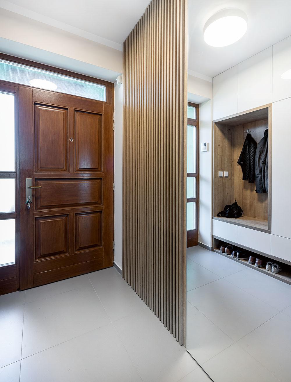 Vpredsieni bolo potrebné vytvoriť dostatok odkladacích priestorov, no zároveň dbať aj na komfort pri obúvaní aobliekaní. Preto sem architekti navrhli vstavanú skriňu snikou na sedenie. Drevenými lamelami na protiľahlej stene zakryli radiátor arozvádzač.