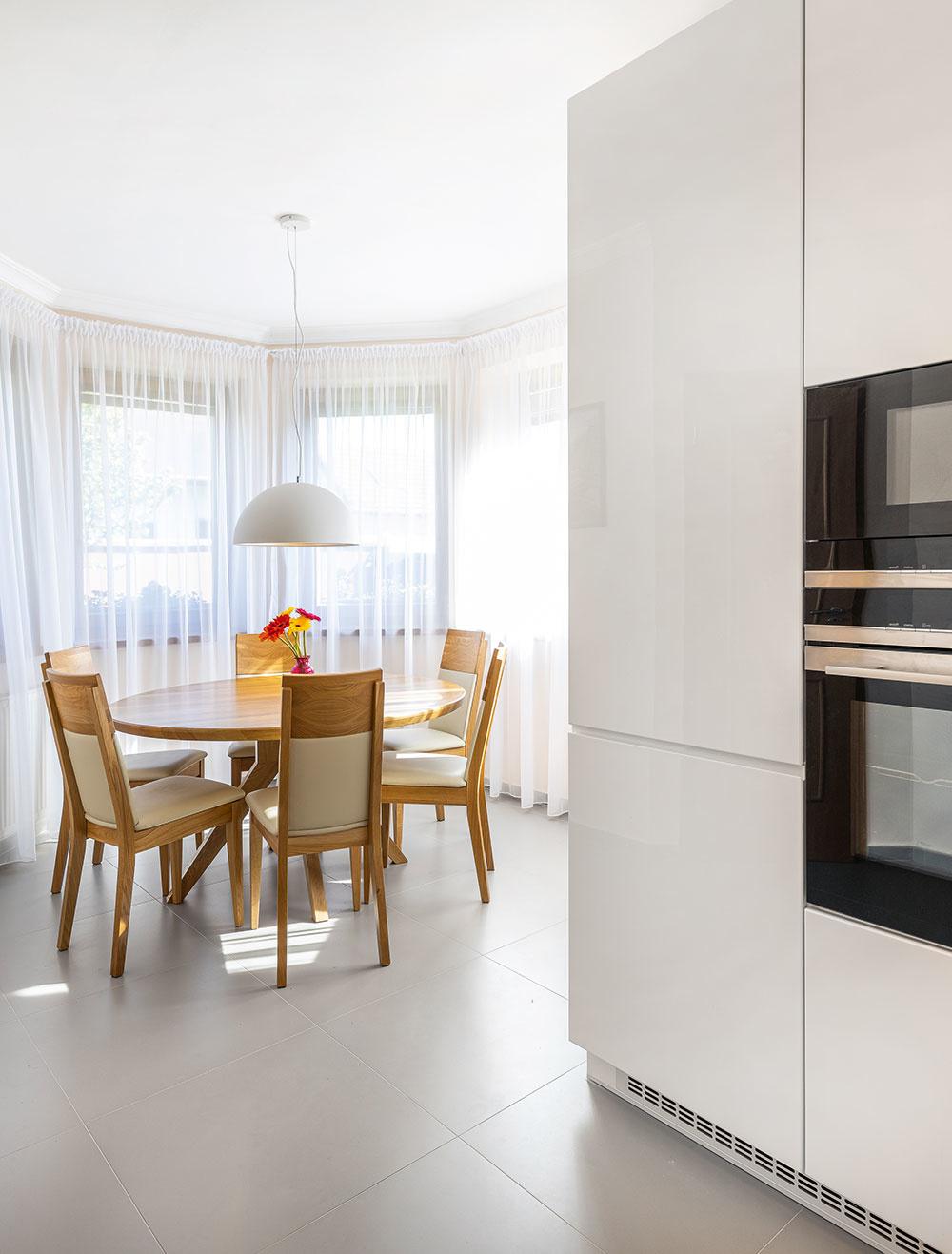 Jedáleň sokrúhlym stolom, čalúnenými stoličkami abielymi závesmi až po zem nadväzuje na kuchyňu. Jednoduché tvary afarebnosť sprevahou bielej dodali interiéru vzdušnosť anavodili pokojnú atmosféru, striedmo aprakticky zariadený priestor sa navyše dobre udržiava.