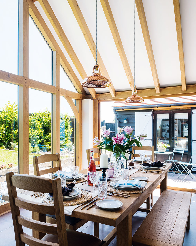 Priznaná konštrukcia zdubového dreva nadväzuje na štýl pôvodného domu avpristavanej časti prirodzene navodzuje pocitútulnosti. Zasklenie, ktoré odľahčuje štítovú stenu jedálne, zároveň vytvára intenzívne spojenie medzi denným interiérom aokolím.