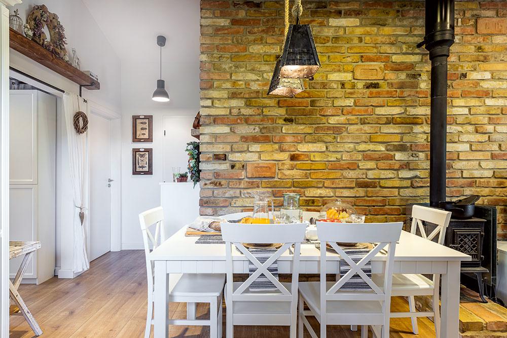 TEHLOVÁ STENA predeľuje priestor na dve časti. Dennú tvoria kuchyňa sjedálenským stolom aobývačka, zktorej sa vychádza na krytú verandu. Vnočnej časti sú dve spálne, kúpeľňa aWC. Tretia spálňa  je vprednej časti domu avchádza sa do nej zchodby.
