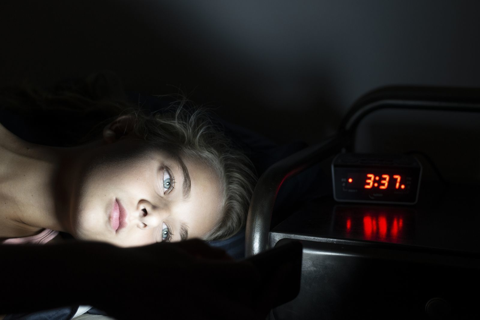 Young teenage girl in bed late at night using her smartphone. Can