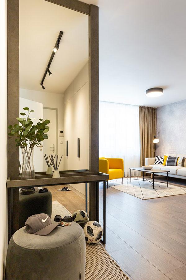 Pri vstupe do bytu pritiahne zrak veľké zrkadlo s konzolovým stolíkom v betónovom dekore a so sivou taburetkou na sedenie, ktoré dávajú tušiť charakter interiéru. Zrkadlo opticky predlžuje úzke zádverie a navyše slúži ako funkčný a praktický doplnok predsiene.