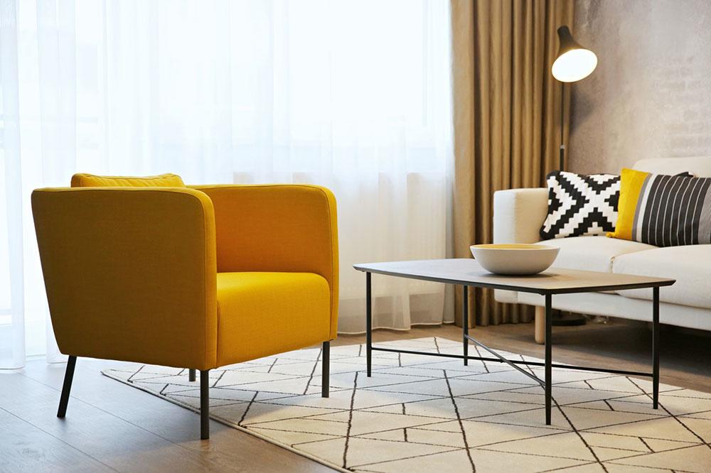Vážny chlapský interiér zjemňuje sedačka v neutrálnom odtieni a otepľujú ho akcenty žltej na vankúšoch, žlté je aj oddychové kreslo.