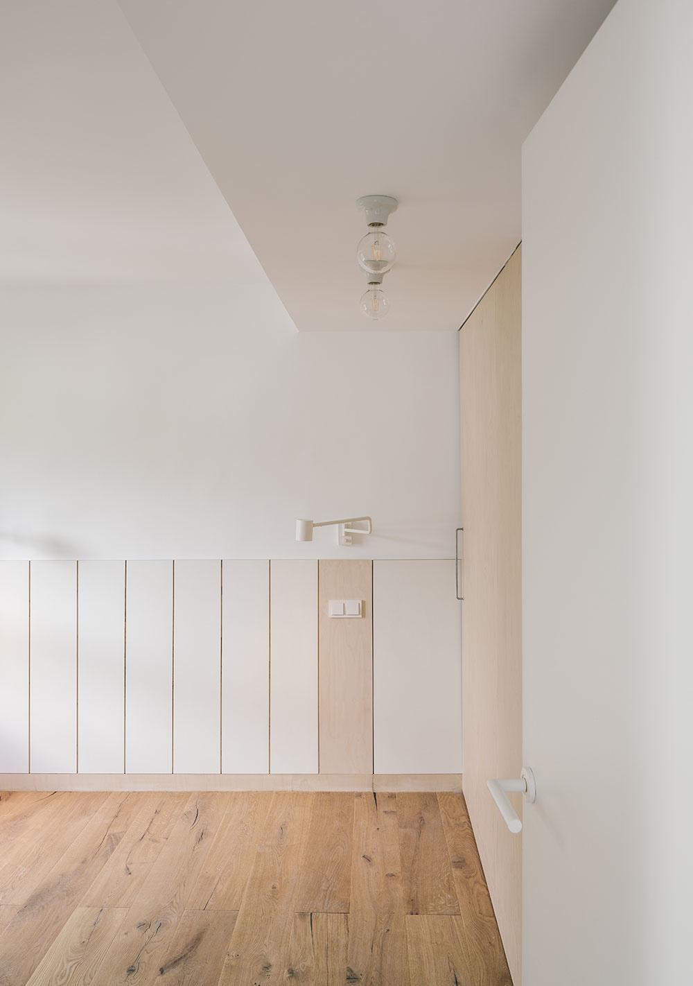 Hlavná spálňa má drevenú podlahu a bielu vstavanú skriňu.