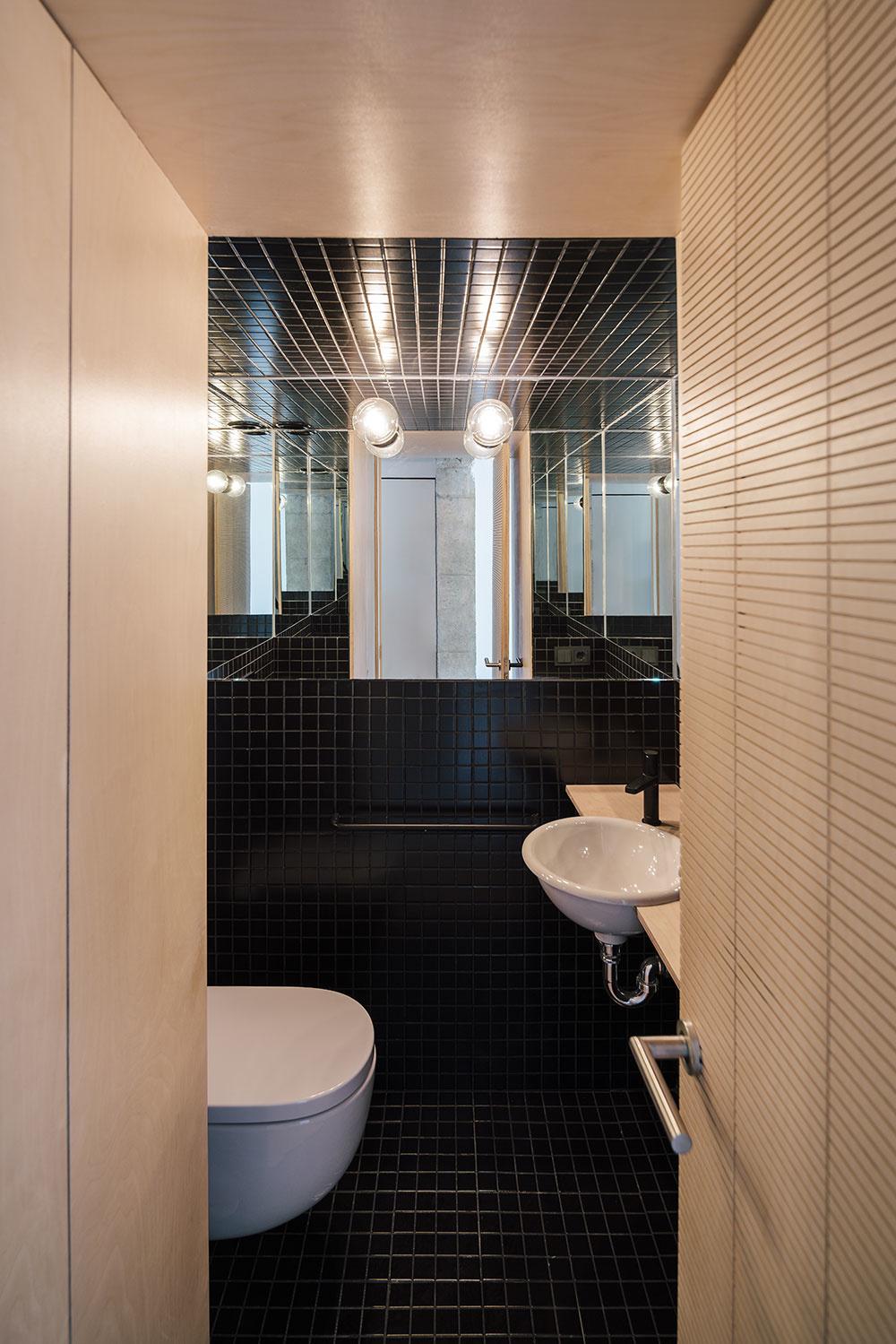 čiernymi obkladačkami obložená toaleta s umývadlom