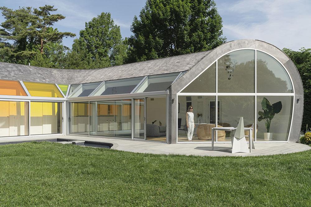 Slnečné lúče sa odrážajú od vodnej nádrže, ktorá je pozdĺž vnútorných ramien domu a cez sklenú fasádu vstupujú do interiéru.