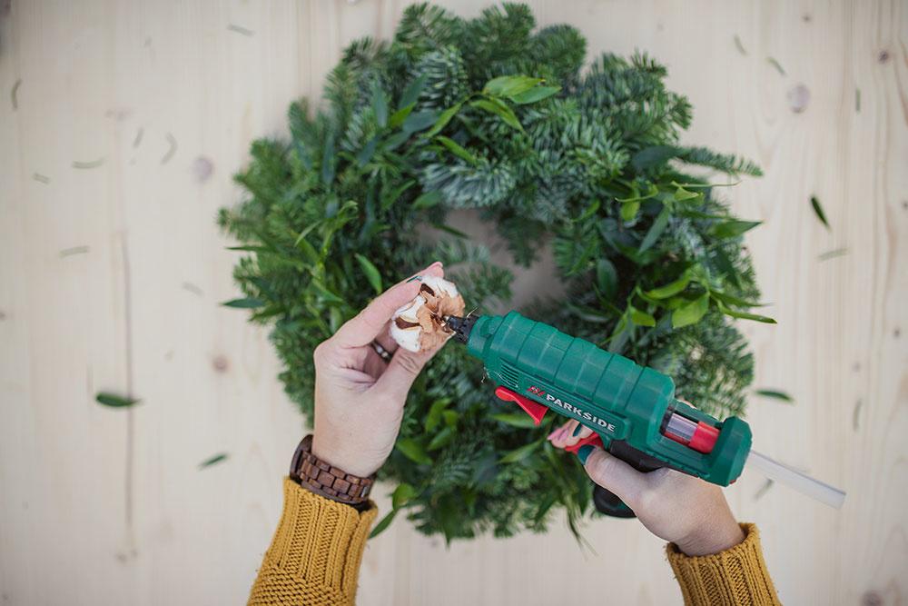 Keď máte základ venca hotový, môžete začať s dekorovaním. Jednotlivé dekorácie nalepte na veniec pomocou taviacej pištole.