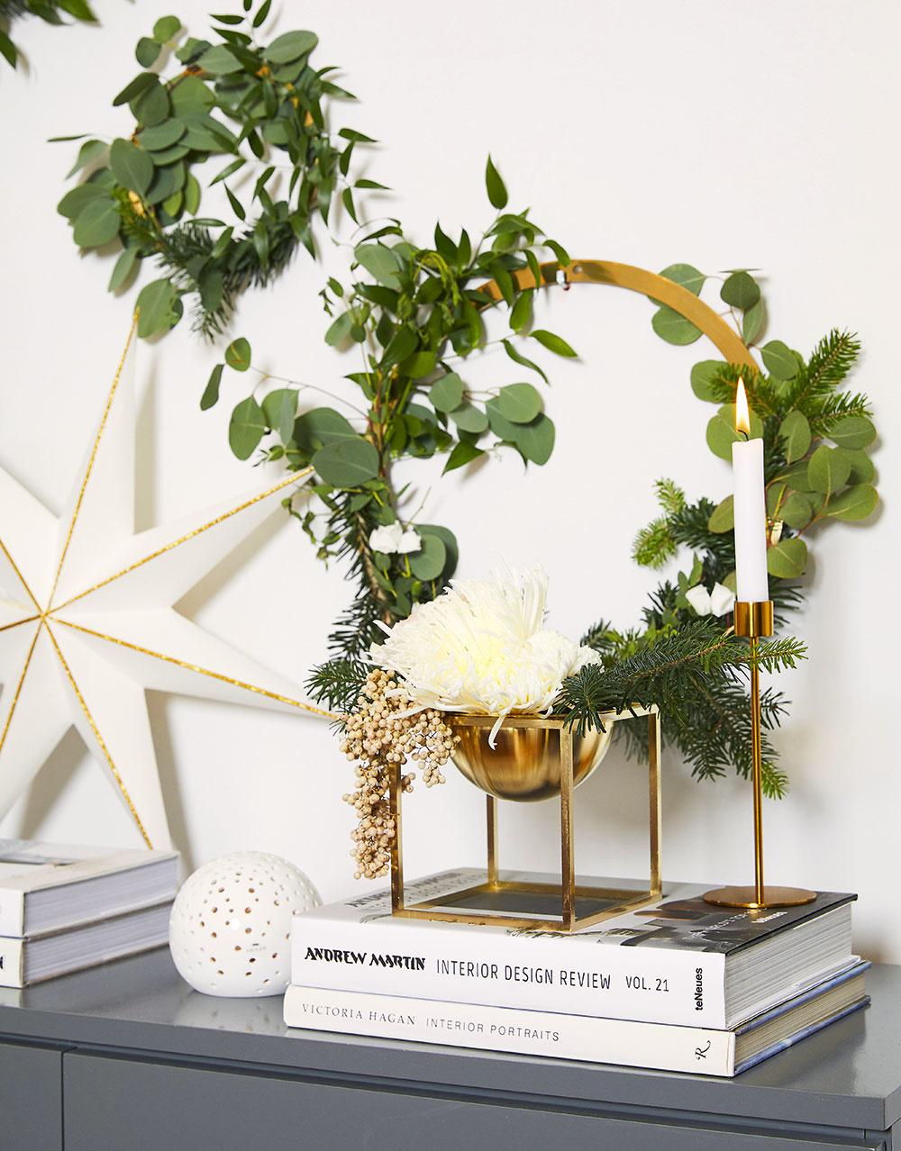 Kovové zlaté kruhy zavesené na klinčekoch nie sú žiadnou novinkou na trhu. Ak ich trochu ozdobíte zelenými vetvičkami, napríklad zrôznych druhov eukalyptu alebo čečiny, získate krásnu zimnú dekoráciu vprírodnom štýle.