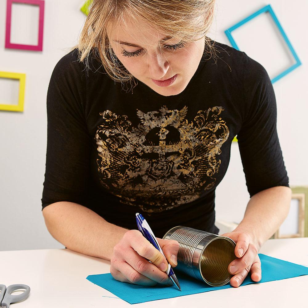 Vymerajte látku. Vyberte si vhodný kúsok hrubšej látky alebo tapety, ceruzkou naň načrtnite obal na plechovku a následne ho vystrihnite.