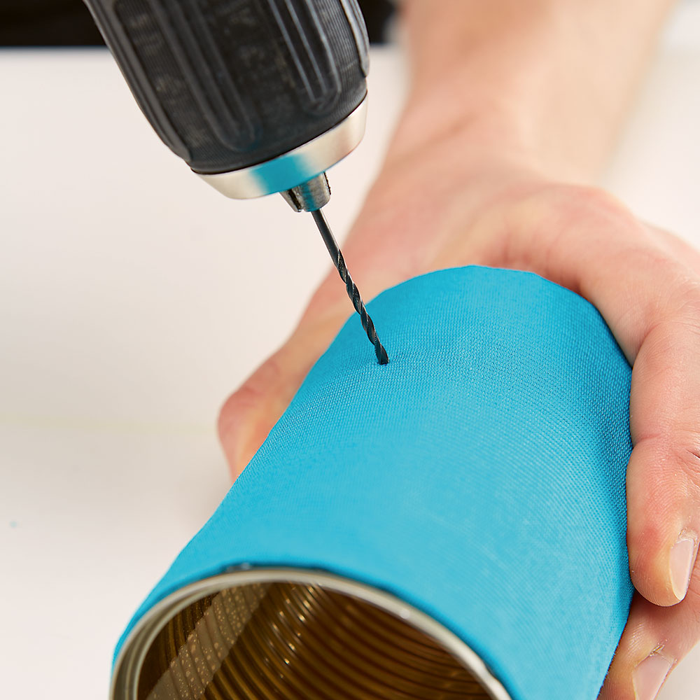 Diery na stojan. Po oboch stranách plechovky si v rovnakej výške predvŕtajte dierky na stojan a dajte do nich skrutky s podložkami.