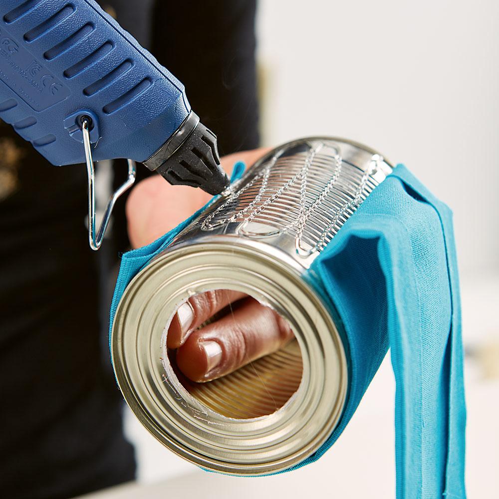 Prilepte látku. Vystrihnutý kus látky alebo tapety potom prilepte pomocou horúcej lepiacej pištole na plechovku a nechajte dobre zaschnúť.