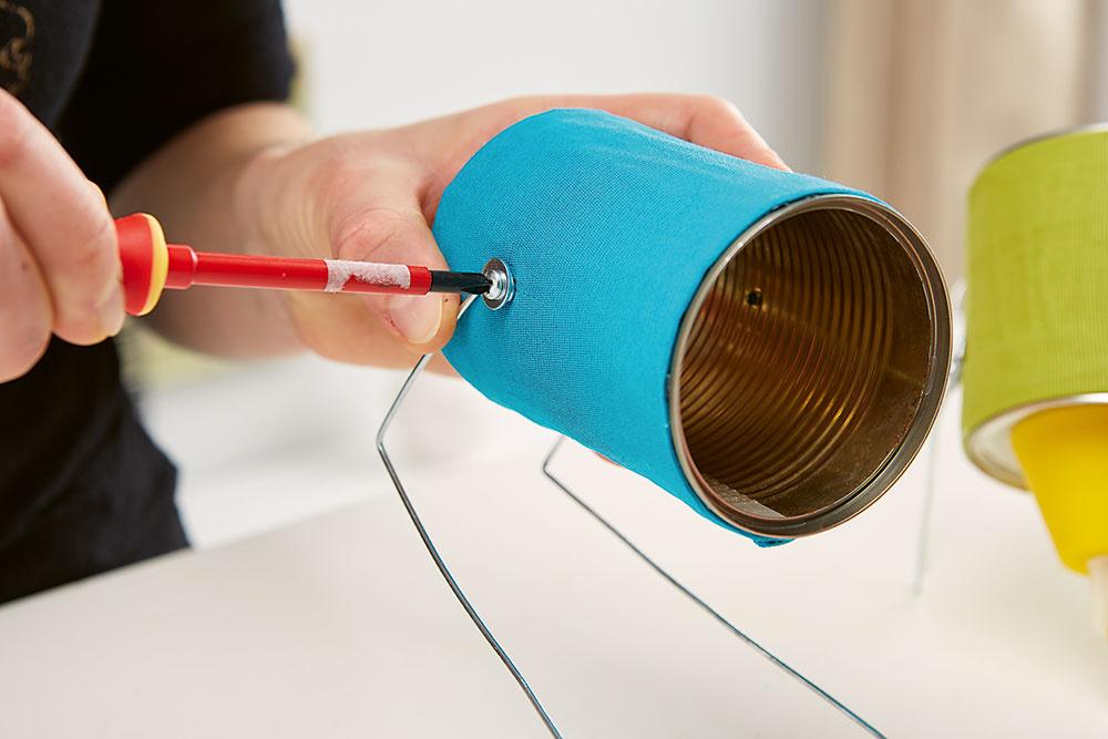 Použite kábel. Nakoniec cez vyvŕtanú dieru prevlečte cez plechovku objímku s káblom na závesnú lampu a zakrúťte do nej žiarovku.