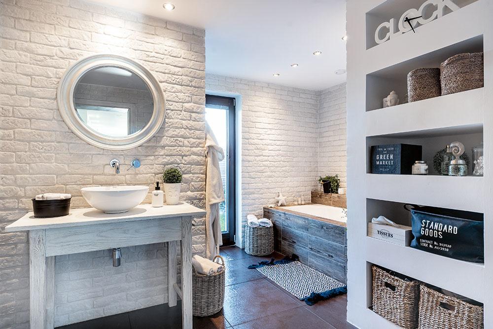 Priestranná kúpeľňa. Je vnej dostatok miesta na vaňu isprchový kút. Vidiecky nádych jej dodávajú biely betónový obklad na stenách, dlažba sdekorom dreva aprekrásne prútené koše.