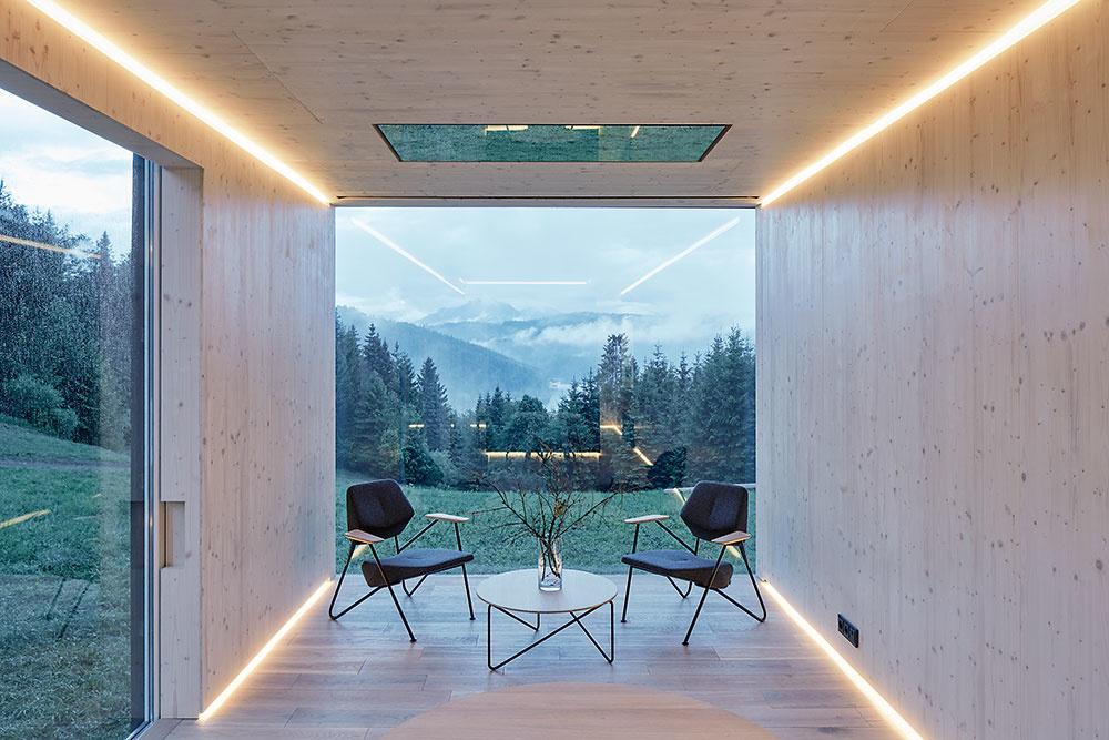 Veľké zasklenia na všetkých piatich stenách modulu rámujú výhľady do prírody, ktorá sa tak stáva súčasťou interiéru. Na dlhšej, vstupnej strane je to otváracia zasklená stena, ktorá dokáže fyzicky prepojiť interiér sokolím, vykonzolovaná čelná stena obrátená kpriehrade je prakticky celá zo skla ana mliečnom skle na strane kúpeľne sa odohráva tieňohra konárov ameniacich sa kontúr lesa.
