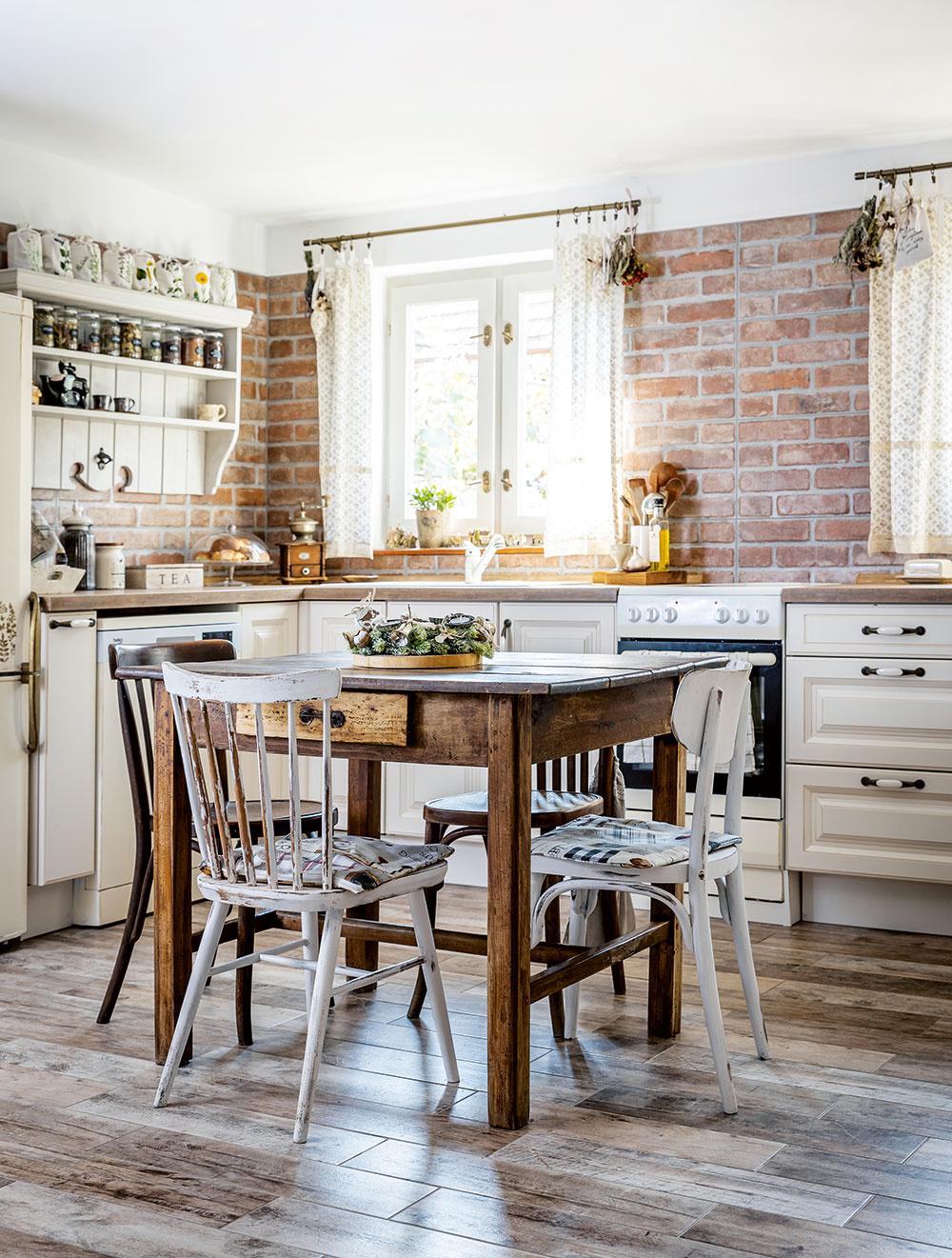 VIDIECKU KUCHYŇU tvoria svetlá kuchynská linka, tehlový obklad na stene a podlaha imitujúca drevo.