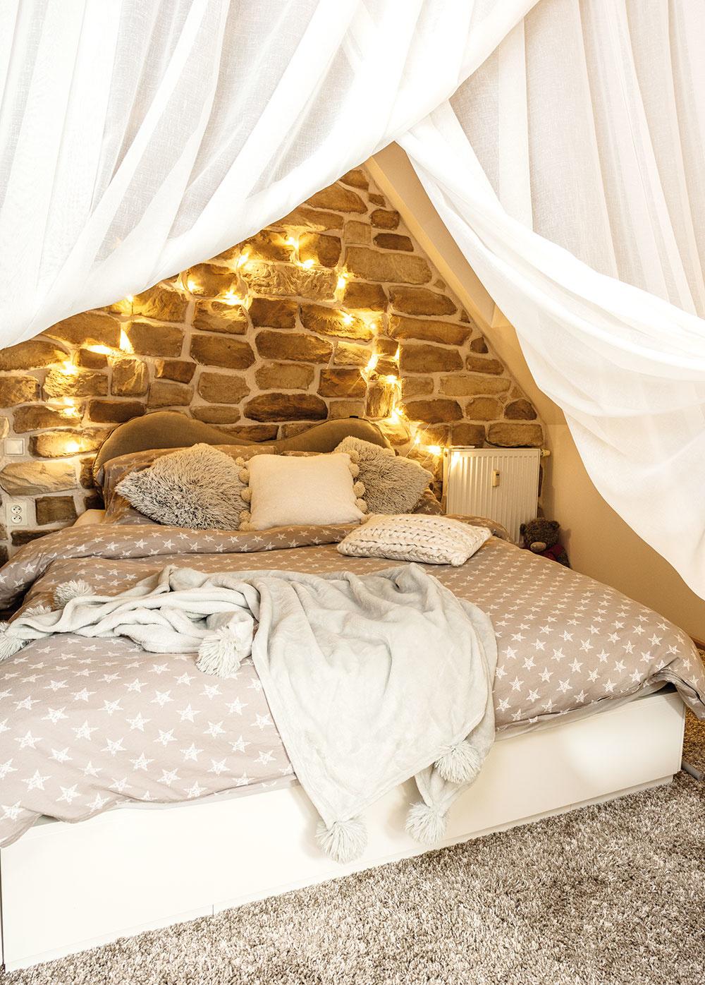 Stena v záhlaví postele v Romaninej spálni je rovnako ako tá kuchynská obložená kameňom. Baldachýn z bielych závesov prispieva k pocitu bezpečného hniezda.
