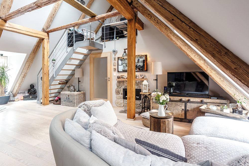 Z otvorenej obývačky na spodnom podlaží vedú kovové schody na poschodie, ktoré majiteľka využíva ako svoju spálňu a pracovňu.