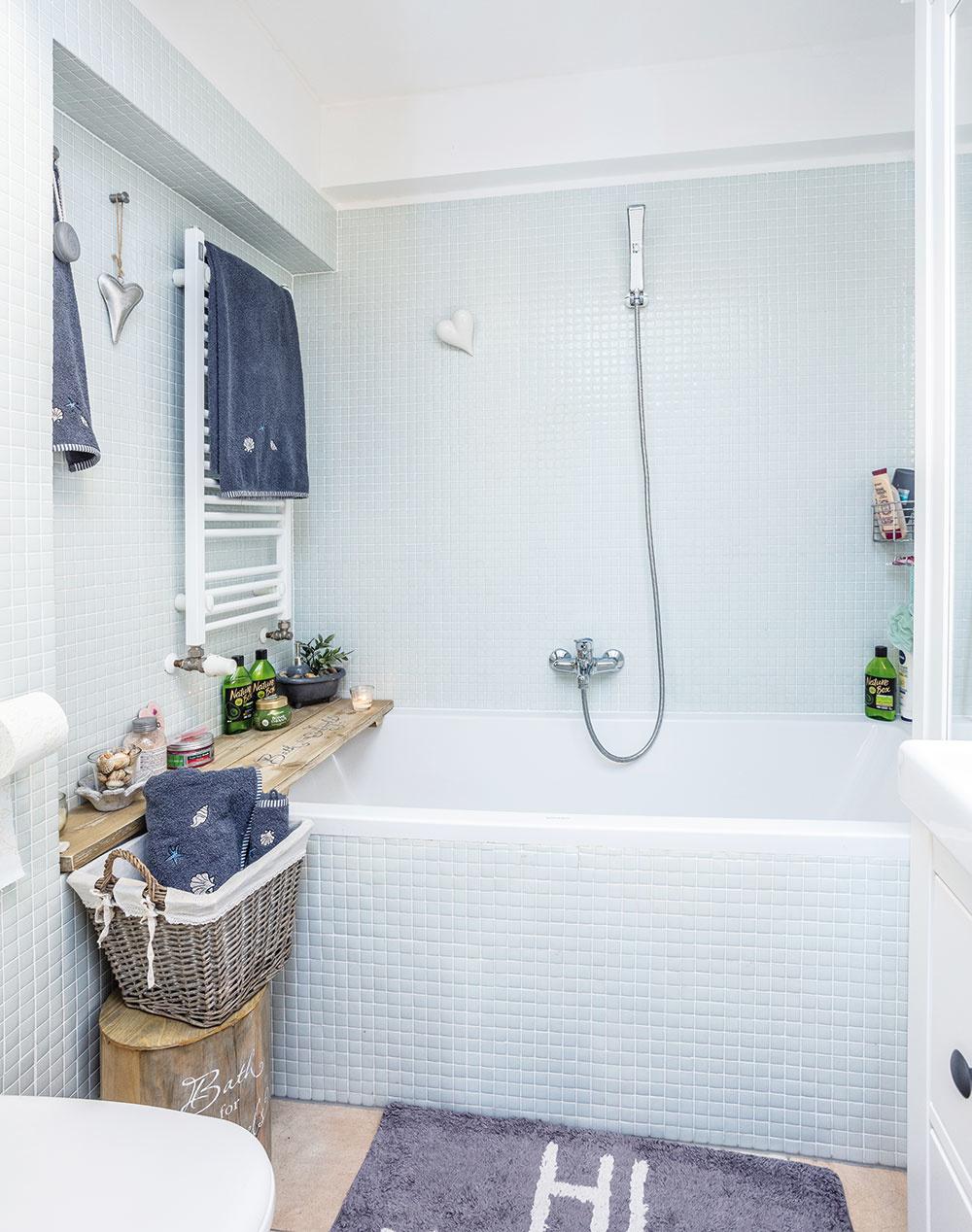 Kúpeľňa je obložená nežnou bielou mozaikou, príjemne ju dopĺňajú drevené a prútené prvky.