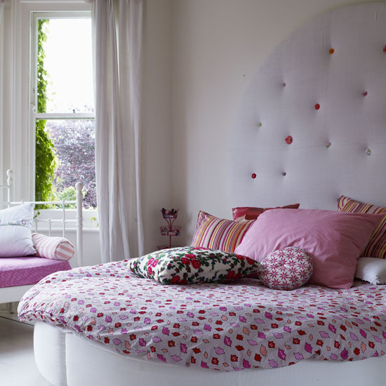 White bedroom round circular bed and button upholstered lilac headboard assorted cushions pink lips duvet real home L etc 02/2009 pub orig