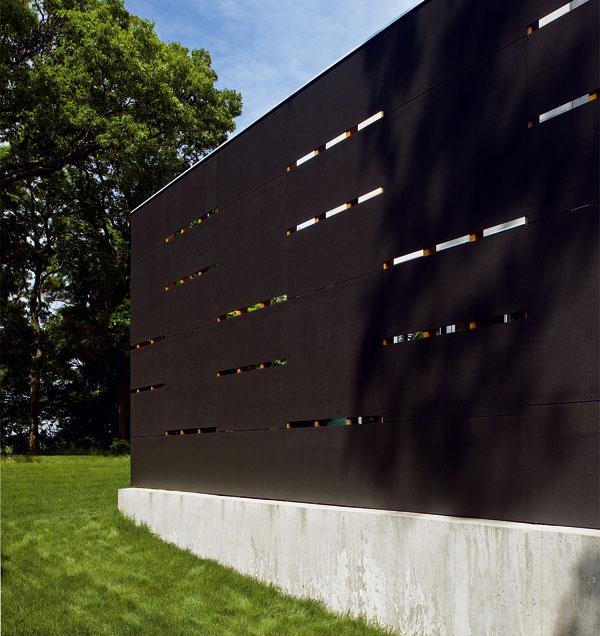 """Na betónovom sokli vyrovnávajúcom sklon terénu stojí iba paravánová stena. Za ňou, ako ukazuje ďalšia fotografia priečelia už sokel nepokračuje a dom v duchu modernistickej klasiky efektne """"visí"""" nad terénom."""