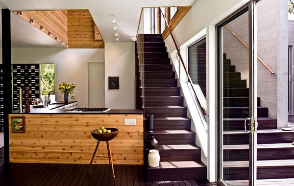 Vďaka impozantným trojdielnym schodom, ktoré potláčajú hranice medzi interiérom a exteriérom, otvorenému priestoru nad kuchyňou, bielym stenám a stropom pôsobí obývacia izba, ktorá má približne päťdesiat metrov štvorcových, ešte priestrannejším dojmom.
