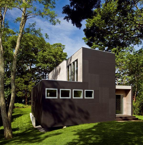 Čisté zelené plochy trávnika bez kvetov a kríkov a kontrast čokoládovej farby a bieleného dreva na prvý pohľad prezrádzajú tendenciu komponovať dom so striedmou škálou prvkov.