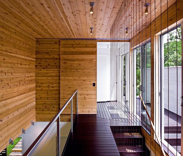 Vstupná časť s kúpeľňou a šatníkom sa, podobne ako spálňa na druhej strane mostíka, dá uzavrieť vysokými dverami. Miesto schodiskovej bariéry sú v úzkych rozstupoch natiahnuté námornícke laná, obľúbený prvok v modernistickej a high-tech architektúre.