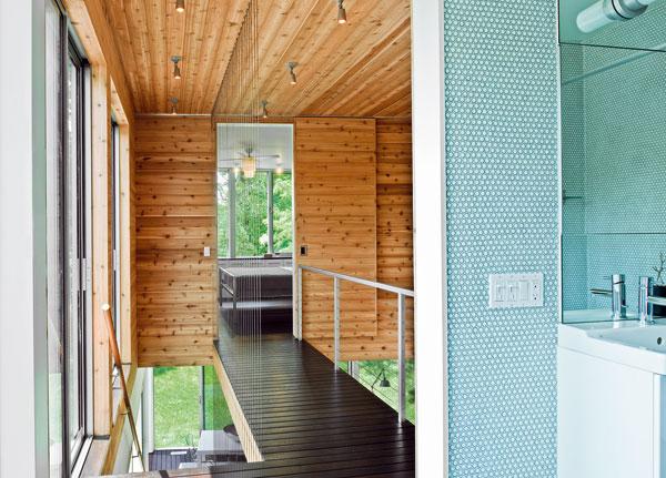 Svieži akvamarínový odtieň, ktorý je tu na kúpeľňových obkladoch, je vlastne v celom dome jedinou protiváhou k svetlej a tmavej farbe dreva, matnému  i lesklému kovu a bielym stenám.