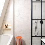 """Industriálny štýl prenikol nenápadne aj do kúpeľne. Pôvodná jednoduchá sbledým obyčajným obkladom dostala celkom inú tvár len vďaka čiernym armatúram asprchovacej zástene včiernom členitom ráme. Oranžový stolček napovedá, že kúpeľňa prislúcha k""""oranžovej"""" spálni."""