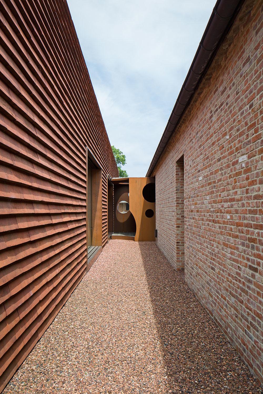 Strecha i fasáda hlavnej budovy sú pokryté 50 centimetrov dlhými červenými dlaždicami bez viditeľných žľabov.