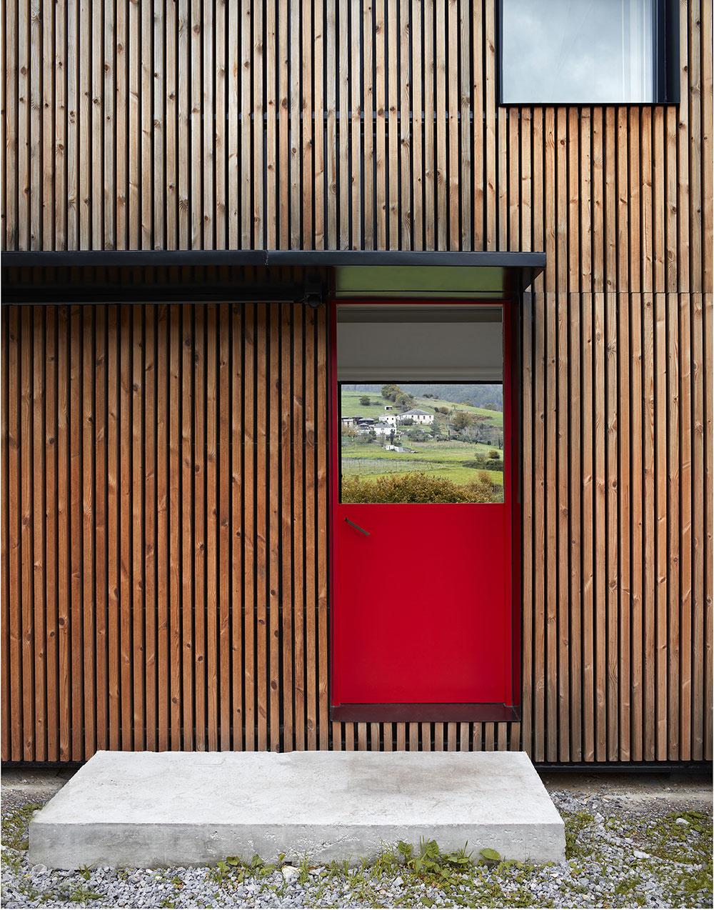 Fasáda domu Montaña je z veľkej časti pokrytá tenkými drevenými latkami v zvislom smere. Oživujú ju červené vstupné dvere.