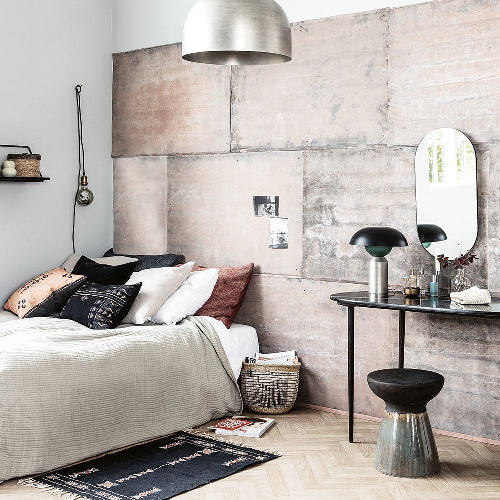 Platne z umelého kameňa – betónu – dodávajú spálni jedinečný štýl. Doplnený je lesklými kovovými a sklenými doplnkami a svetlými drevenými parketami.